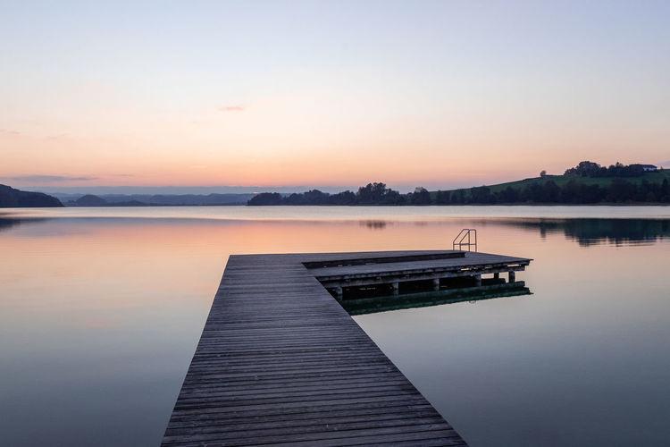 Pier on lake against sky during sunset