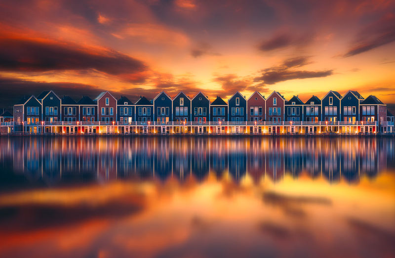Houses Reflecting On Calm Lake Against Orange Sky During Sunset