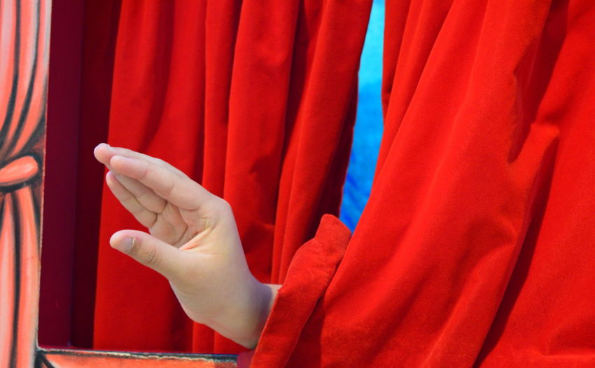 Cropped image of hand gesturing amidst curtains