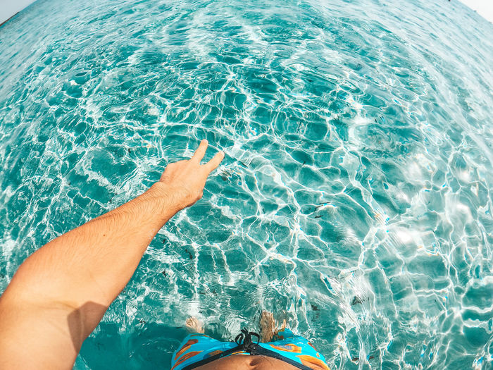 Low section of person in sea by swimming pool