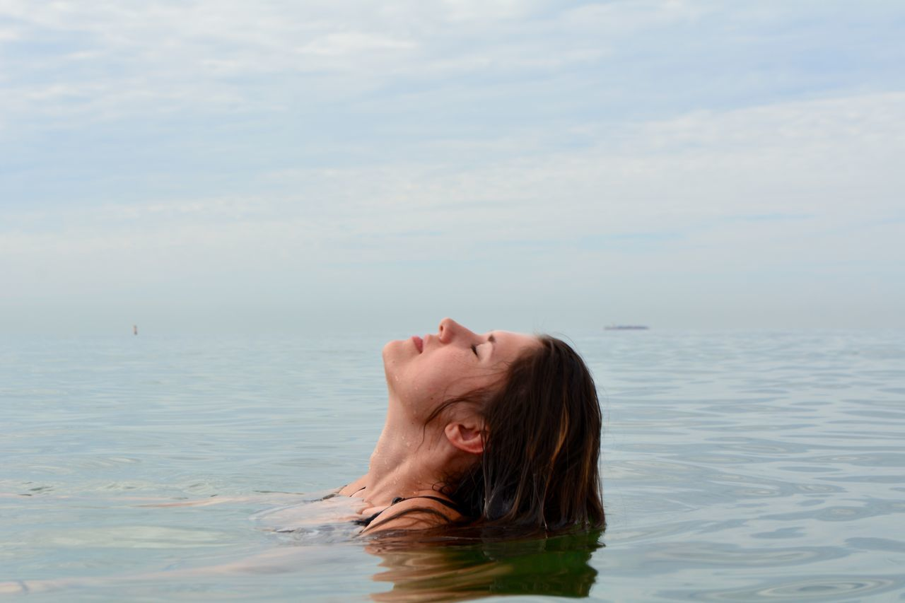 Close-Up Of Woman Swimming In Sea Against Sky
