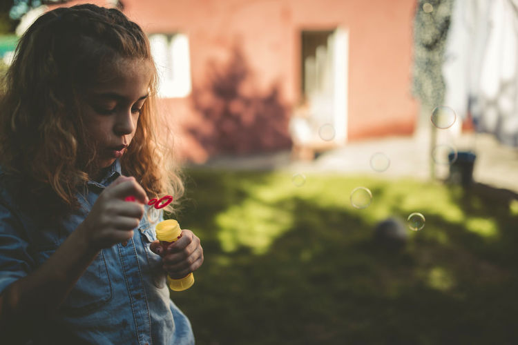Close-up of girl blowing bubble in yard