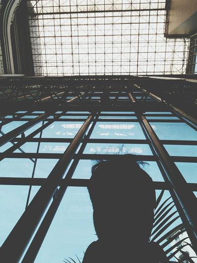 Low angle view of silhouette man against sky seen through window