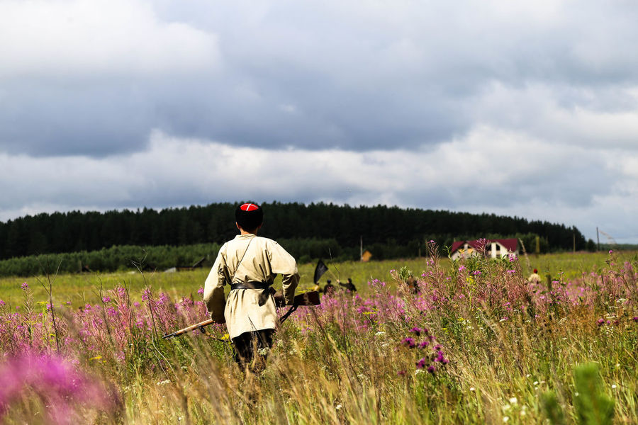 Historical reconstruction of Russian Civil war in the Urals in 1919. Soldier Of The White Army Civil War Russia Soldier Adult Adults Only Beauty In Nature Civil War History Day Field Flower Growth Historical History Landscape Men Military Uniform Nature Only Men Outdoors People Plant Rear View Sky War Weapon