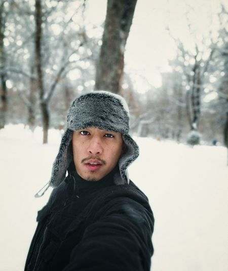 Portrait of man wearing fur hat while standing against bare trees during winter