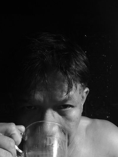 Close-Up Portrait Of Man Drinking Against Black Background