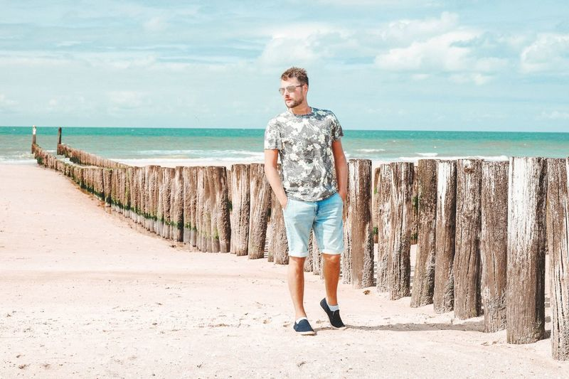 Full length of man walking at beach during sunny day