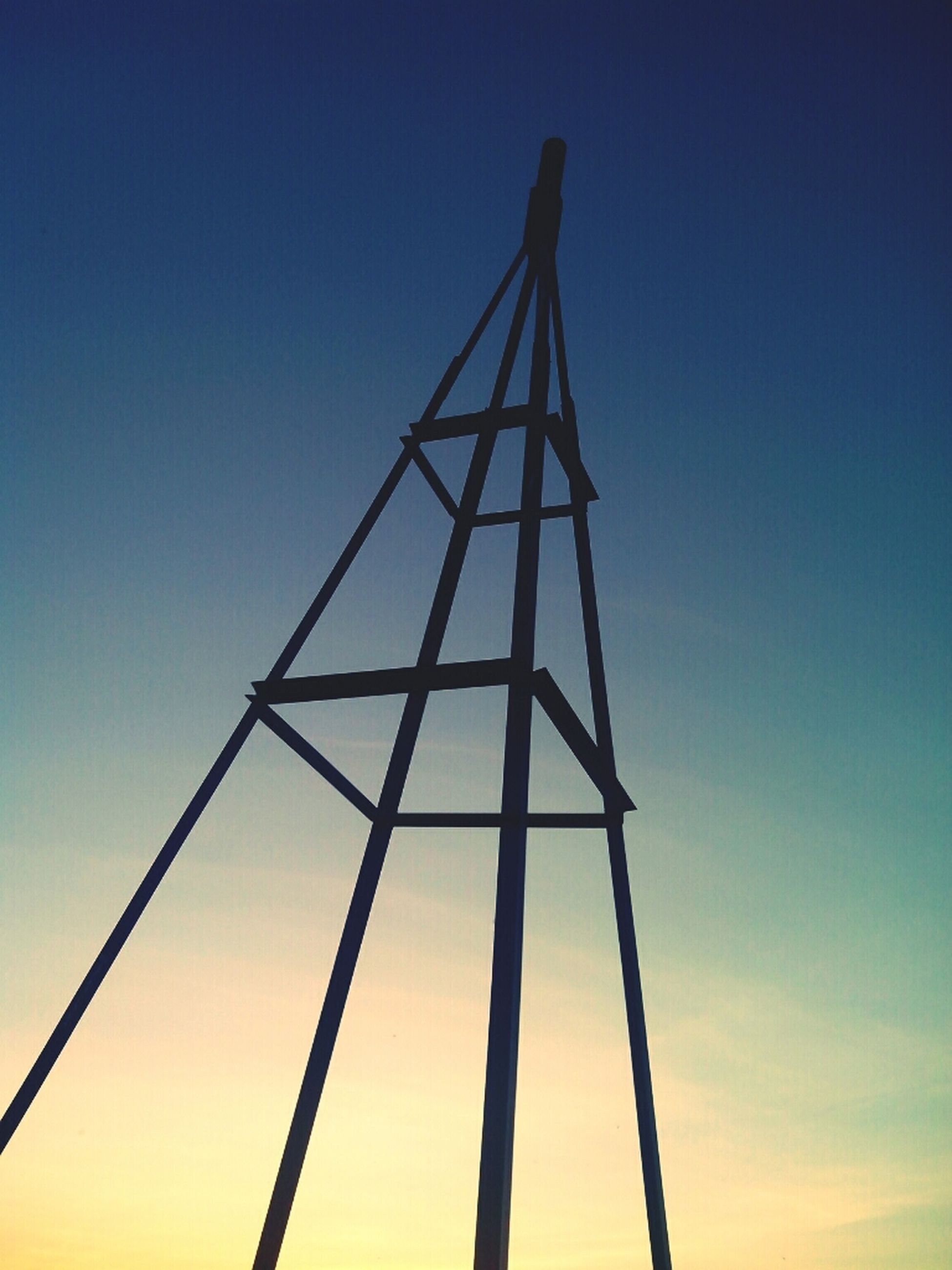 low angle view, sunset, clear sky, metal, blue, sky, fuel and power generation, connection, silhouette, technology, metallic, orange color, no people, electricity pylon, electricity, outdoors, copy space, construction site, power supply, nature