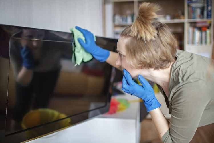 Woman cleaning television at home