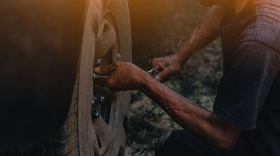 Wheel Change Close-up Day Effort Focus On Foreground Hand Holding Human Body Part Human Hand Lifestyles Mechanic Men Occupation One Person Real People Repairing Skill  Tire Transportation Wheel Wood - Material Working Wrench