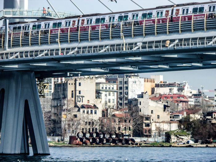 Train On Railway Bridge Over River In City