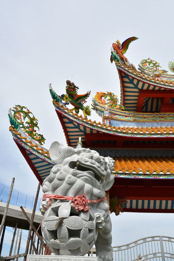 Low angle view of sculptures and roof of bang pa-in royal palace against clear sky