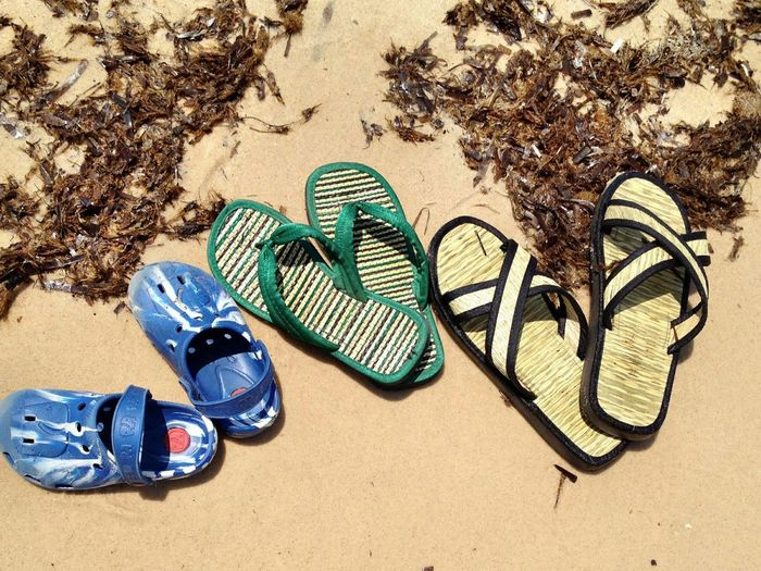 High angle view of slippers at sandy beach