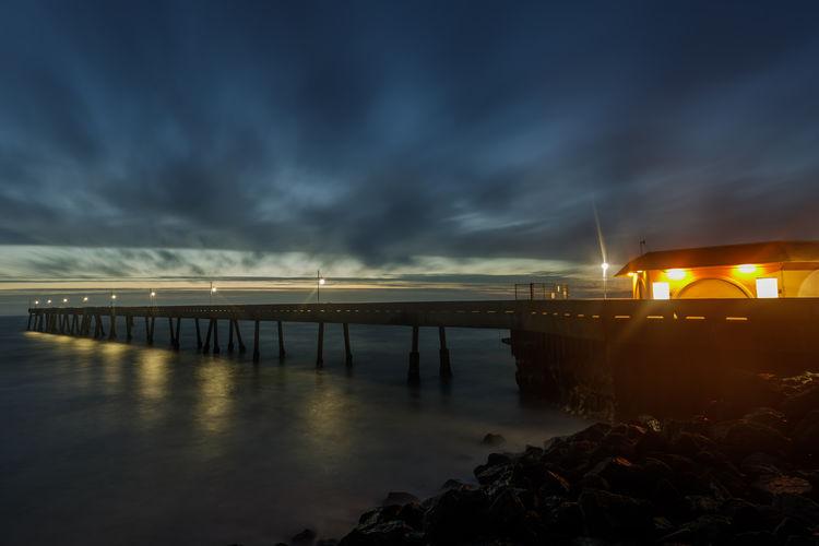 Bridge over sea against sky at night