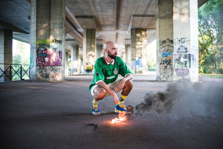an Italian-Mexican singer perfectly at ease in his urban fire hadn't actually been planned, but he was very professional and kept on playing his role City Colors Fashion Football Green Mexico Milan Milano Singer  The Fashion Photographer - 2018 EyeEm Awards Beard Burning Denim Fashion Photography Fire Italian Style Lifestyles Men Rap Rapper Sneakers Socks Streetphotography Urban Urbanphotography