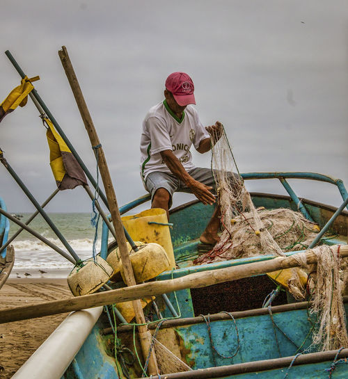 Man fishing in boat against sea