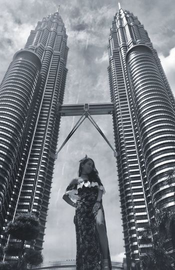 Low angle view of woman standing by petronas towers