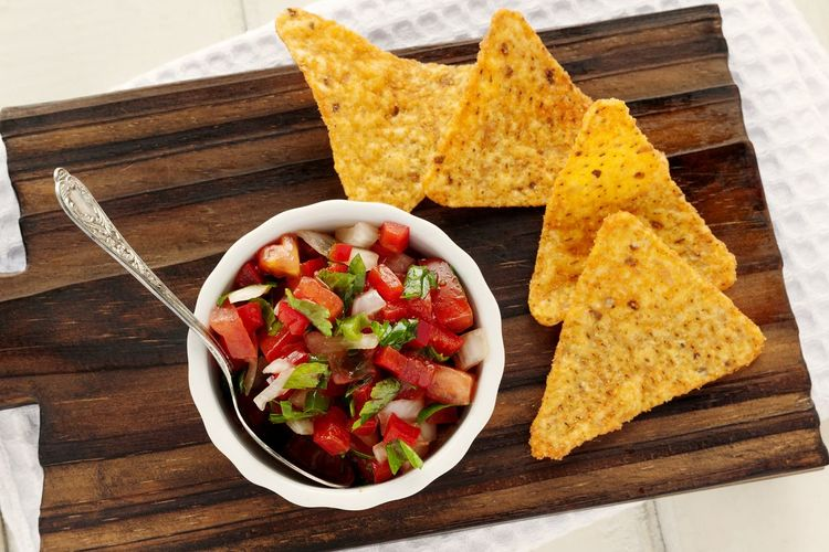 Pico de gallo salsa with nachos on cutting board. Vegetable Bowl Healthy Eating Pico De Gallo Studio Photography UnykaProductions Mexican Food Texmex Food Salsa Texmex Red Bell Pepper Tomato Cilantro Parsley Onion Colorful Nachos Appetizer DIP Natural Light Nachos Cutting Board White Napkin White Background Wooden Background