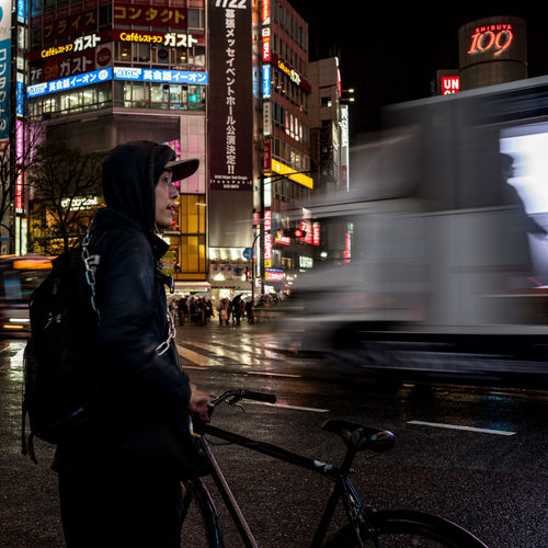 Blurred motion of man standing on road at night