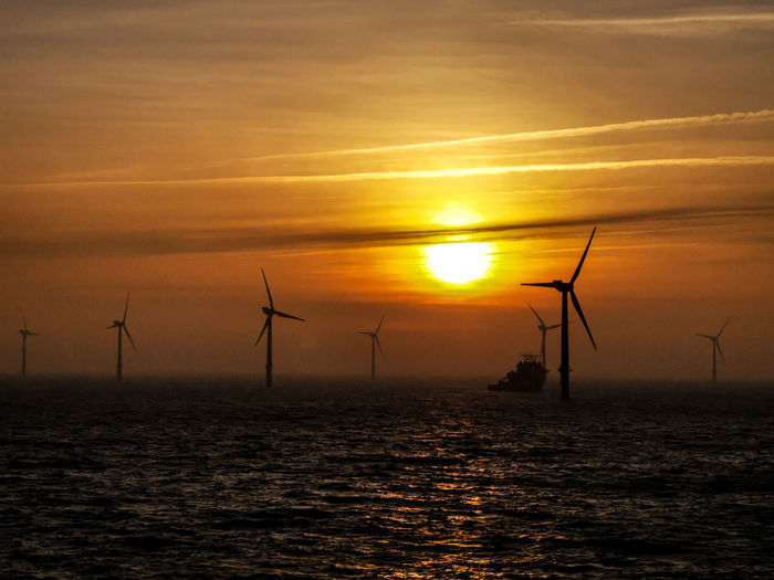 Silhouette of wind turbines in sea during sunset