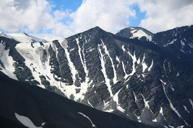 Dark rocky mountains with snow in altai in summer in fine weather