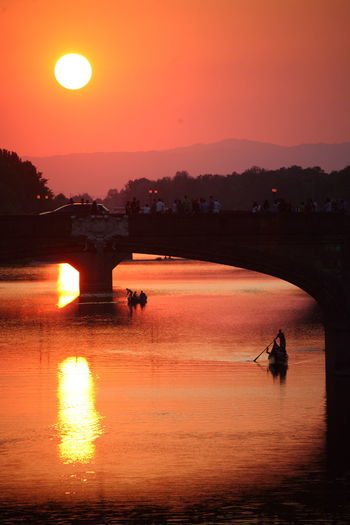 Silhouette of bridge and rowing boats