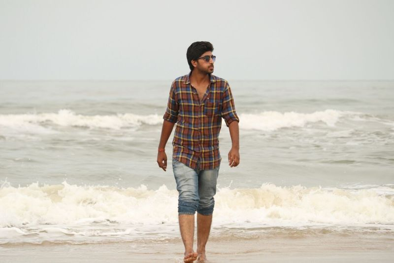 Full length of man walking on shore at beach against sky
