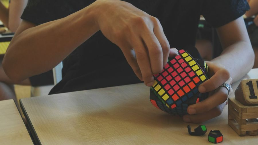 Midsection Of Person Fixing Puzzle Cube On Table At Home