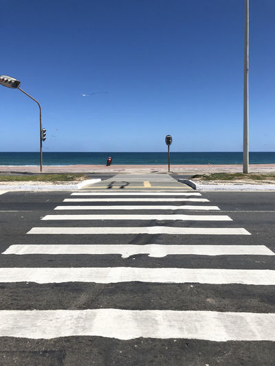 Zebra crossing on road by sea against clear sky