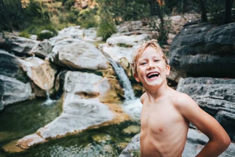 Portrait of happy shirtless boy standing by stream in forest