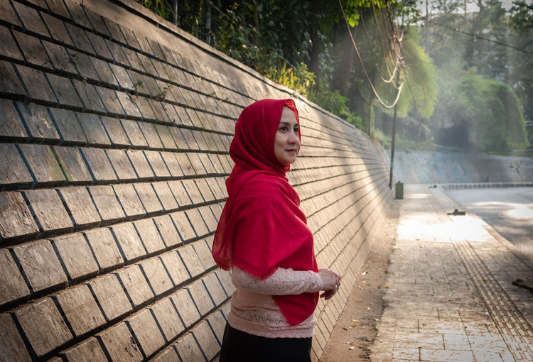 Portrait of woman standing on footpath