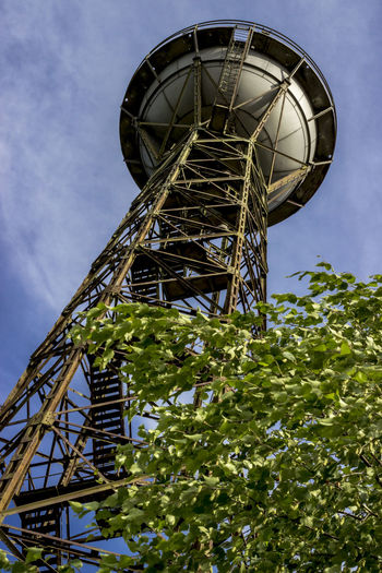 Low angle view of metallic water tower against sky