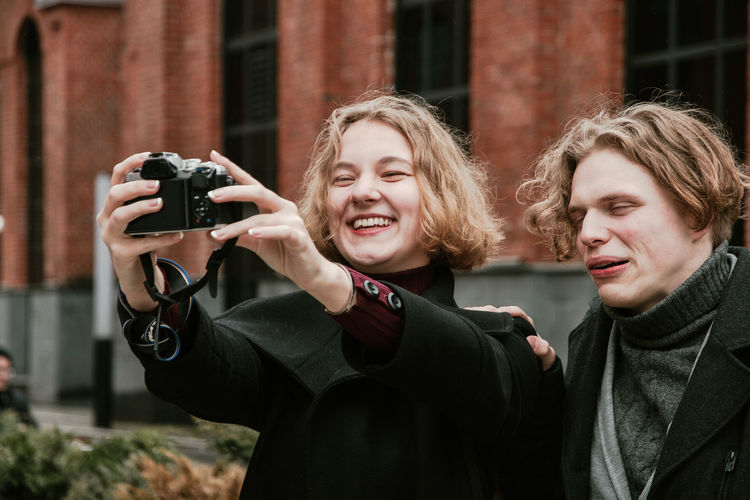Happy friends photographing themselves with digital camera