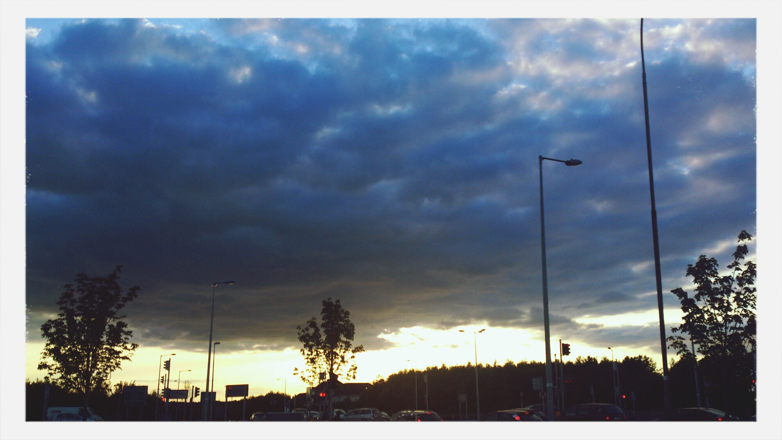 sky, transfer print, cloud - sky, silhouette, tree, cloudy, building exterior, auto post production filter, low angle view, built structure, cloud, architecture, street light, overcast, weather, dusk, sunset, outdoors, nature, city