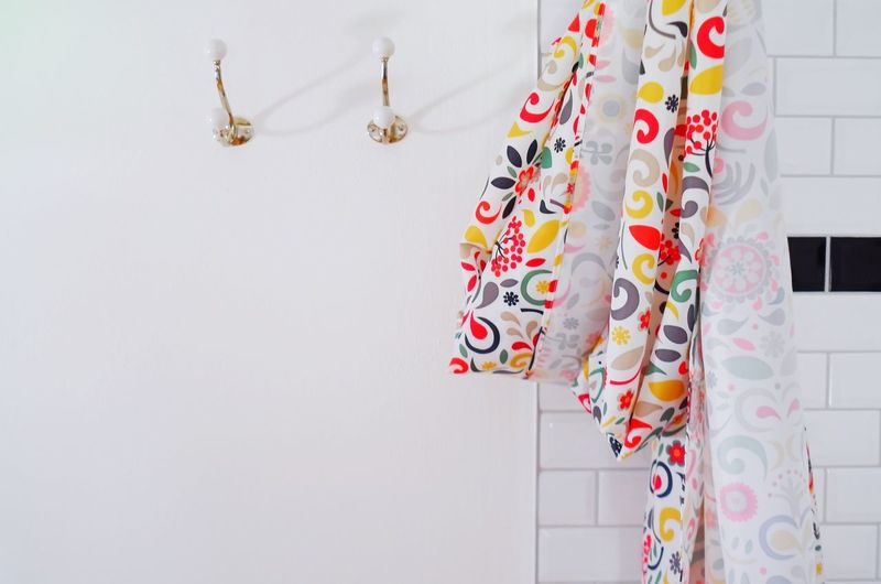 Close-up of multi colored curtain hanging against wall
