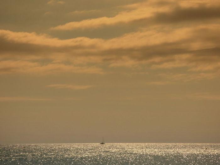 Remote ship sailing on sea at sunset