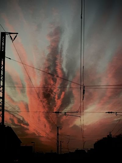 Low angle view of silhouette cables against sky at sunset