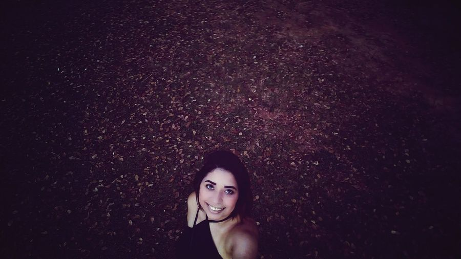 High angle view of smiling young woman standing on field