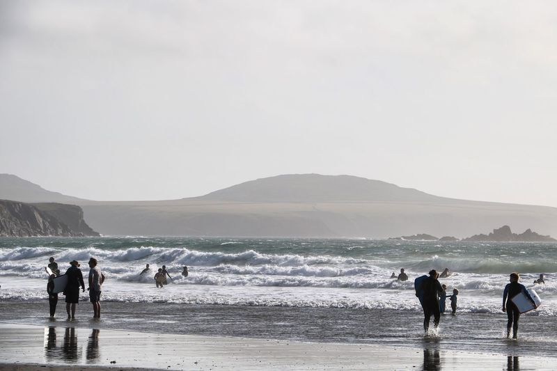 People enjoying at beach by mountain against clear sky