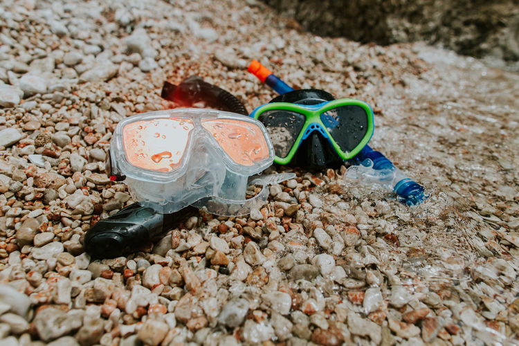 Snorkelling masks on pebble beach. Two diving masks and snorkels with drops of water washed by sea waves. Snorkeling Snorkel Snorkelling Goggles Diving Mask Beach Sea Summer Pebble Reflection Copy Space Orange Color No People Tube Bright Outdoors Breathe Transparent Blue Color Green Color Horizontal Getaway  Sunny Rocky