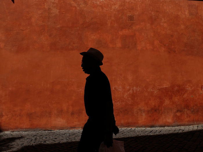 Silhouette man walking against wall