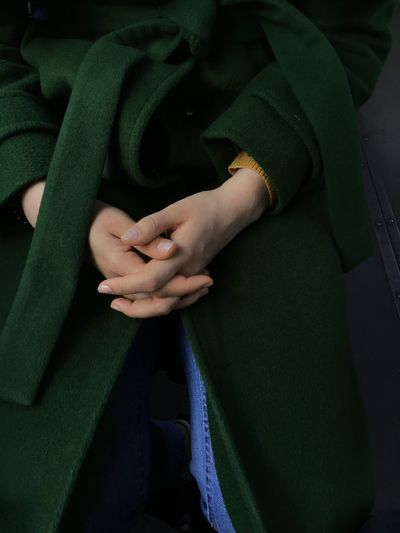 Close-up midsection of woman with hands clasped