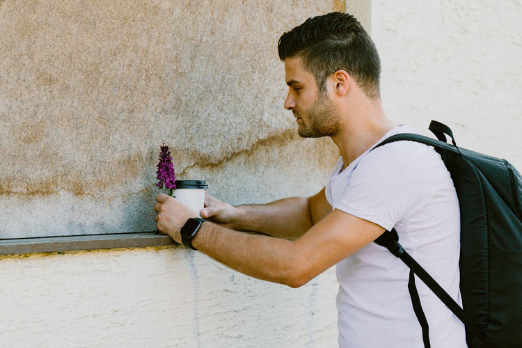 Side view of young man looking away against wall