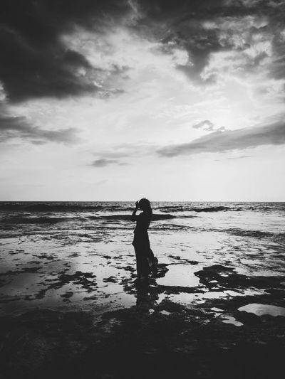 Silhouette woman standing at beach against sky