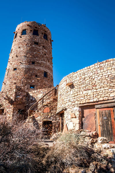 Desert View Tower at Grand Canyon Arizona Brick Wall Desert View Tower Grand Canyon Architecture Blue Building Building Exterior Built Structure Clear Sky Day History Low Angle View No People Old Outdoors Sky Sunlight The Past Travel