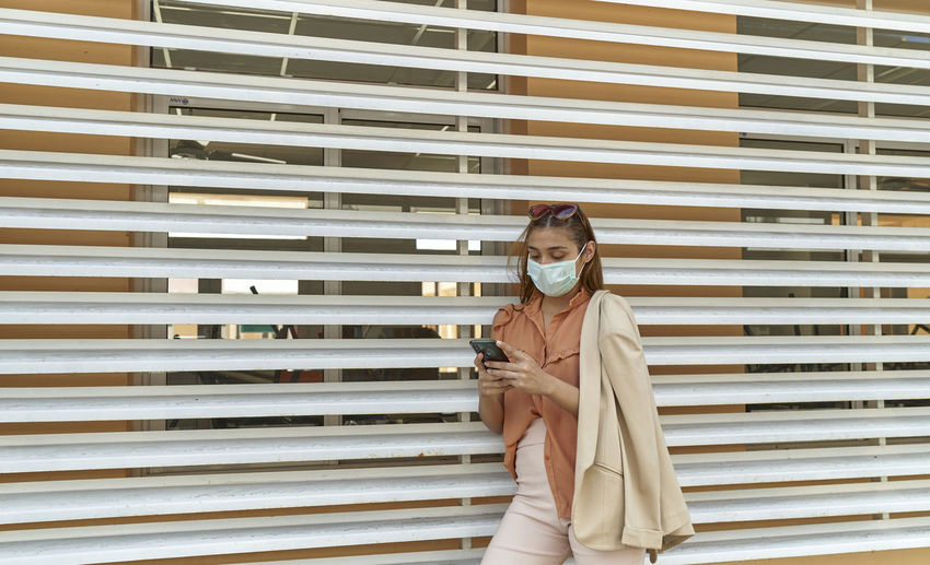 Young business woman wear face mask protect of coronavirus standing at modern office. covid-19
