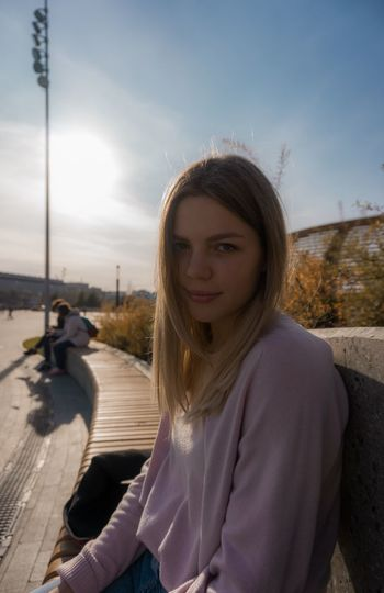 Portrait of beautiful woman sitting on road against sky