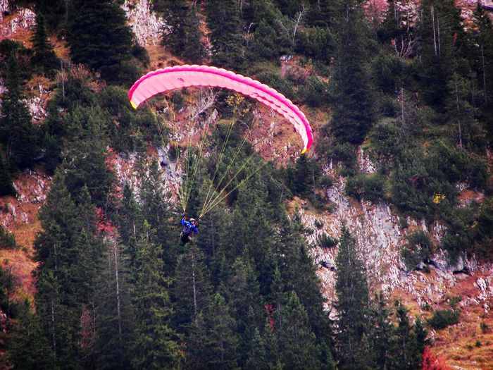 Man paragliding against mountain