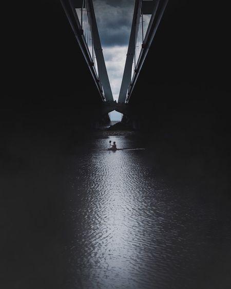 Silhouette bridge over river against sky