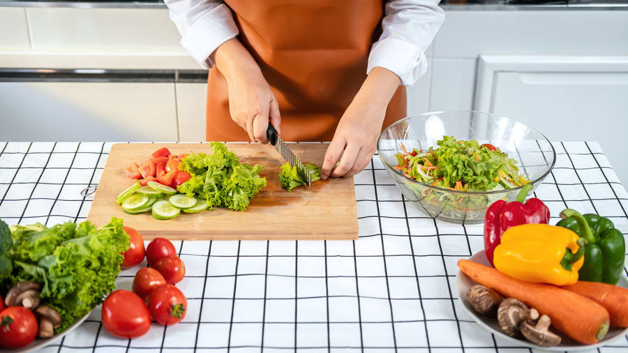 Midsection of man with vegetables on cutting board